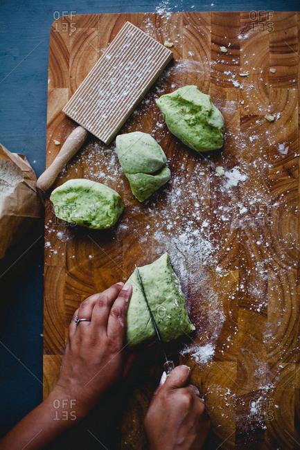 Person cutting green dough to make gnocchi