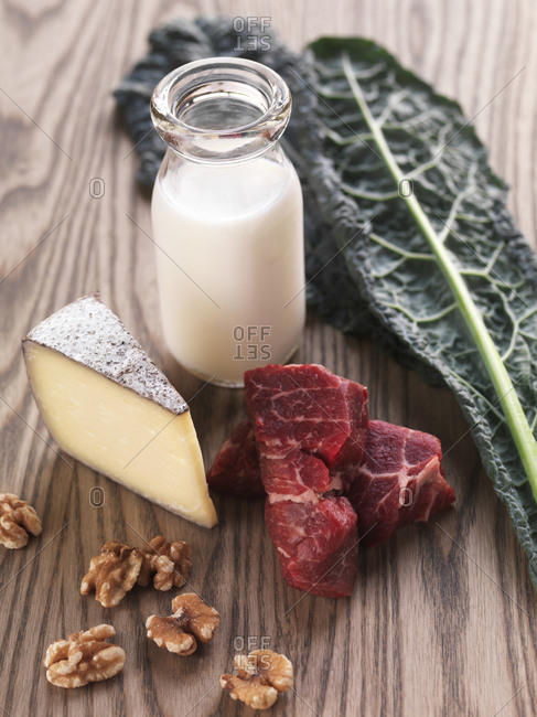 Still life with steak, kale, whole milk, walnuts and cheese