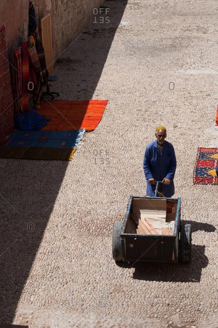 Essaouira, Morocco - May 20, 2008: Man pushing a cart through a market in Morocco
