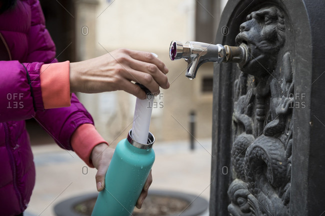 Woman filling bottle with water from water fountain, Cornudella de Montsant, Catalonia, Spain