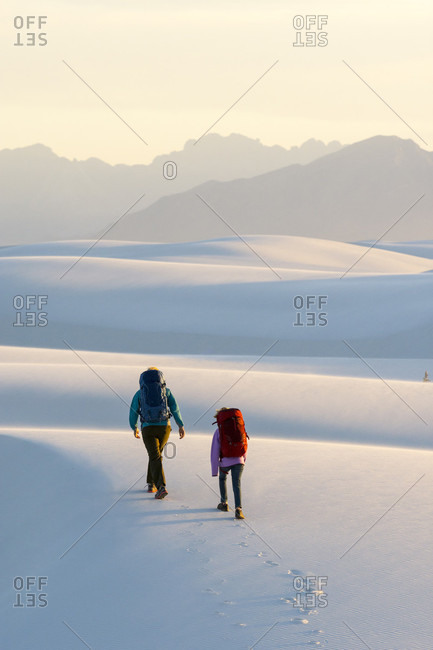 Rear view of woman and girl hiking in White Sands National Monument, Alamogordo, New Mexico, USA
