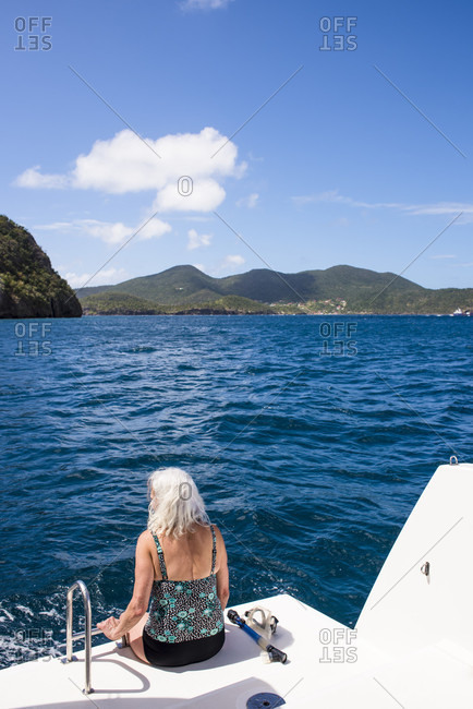Rear view of mature woman with gray hair about to go snorkeling from boat, Bourg de Saintes, Isles des Saintes, Guadeloupe