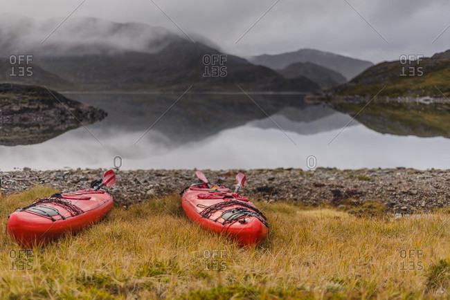 Two kayaks on shore of fjord during tour with Tasermiut Expeditions, Narsaq, Greenland