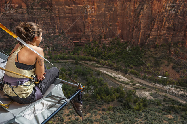 Young woman sitting on portaledge and looking at view while rock climbing Moonlight Buttress, Zion National Park, Utah, USA