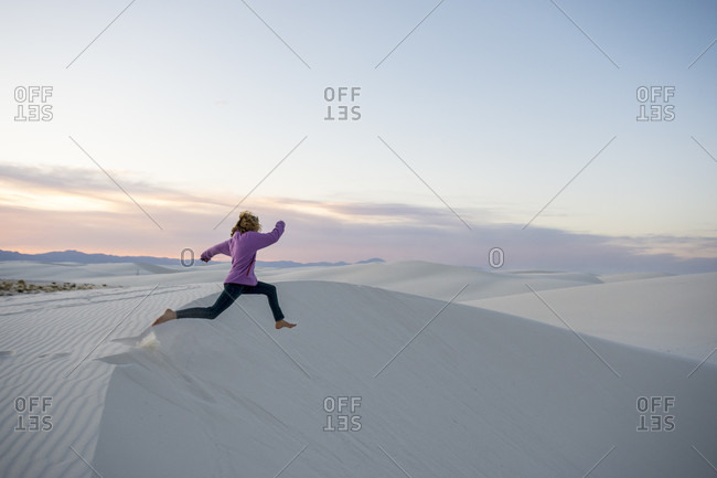 Side view of girl jumping off sand dune in White Sands National Monument, Alamogordo, New Mexico, USA