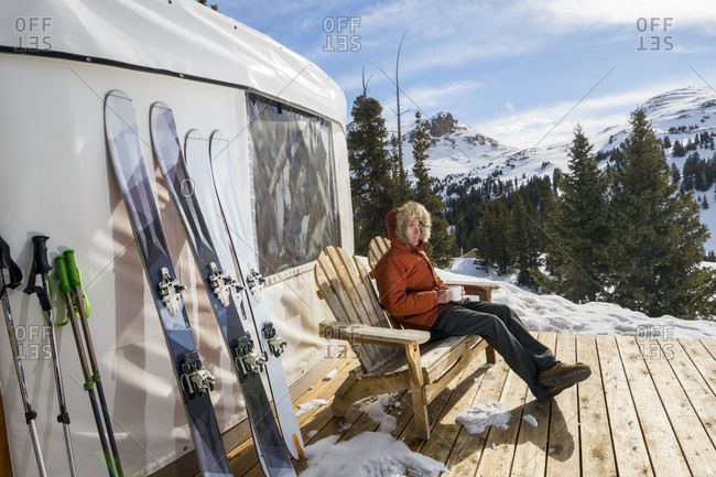 A man sitting on the deck of a yurt drinking tea while camping on Red Mountain Pass, San Juan National Forest, Silverton, Colorado, USA