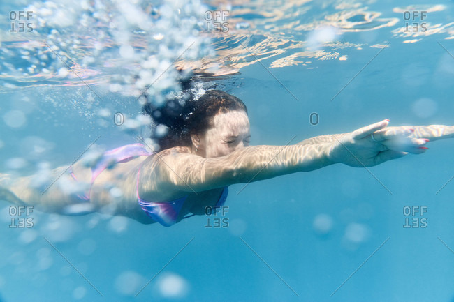 Underwater view of woman in bikini swimming