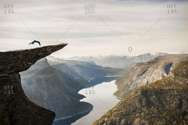 Distant view of person doing backflip on Trolltunga cliff, Hordaland county, Norway