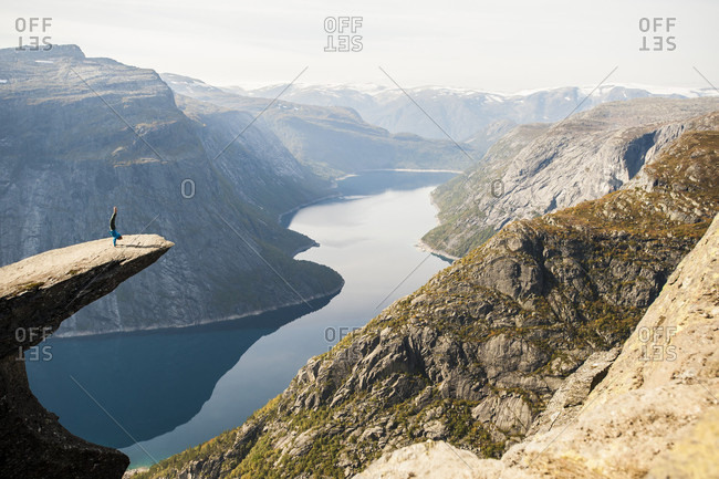 Distant view of person doing handstand on Trolltunga cliff, Hordaland county, Norway