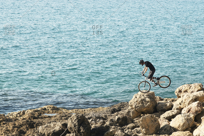 Distant side view shot of adventurous mountain biker doing tricks on rocky coastline