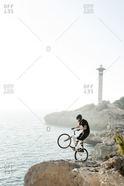 Side view shot of adventurous mountain biker doing trick of lifting front wheel on seashore