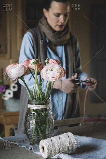 Woman arranging fresh flowers- cutting cord