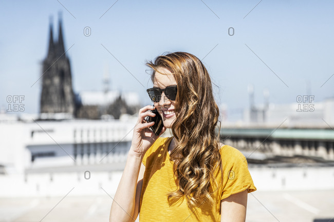 Germany- Cologne- portrait of smiling woman on the phone