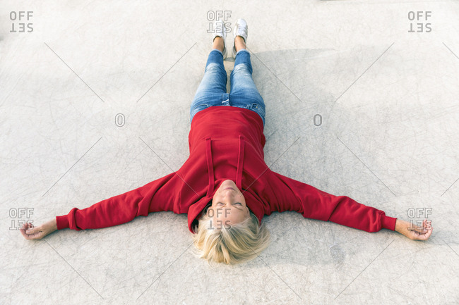 Senior woman wearing red hoodie lying on the ground outdoors