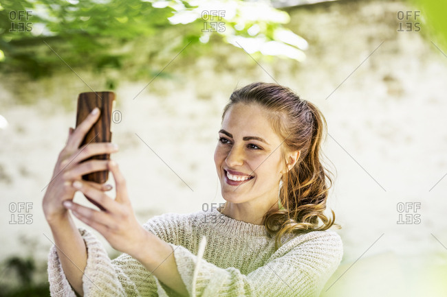 Portrait of relaxed woman taking selfie with cell phone