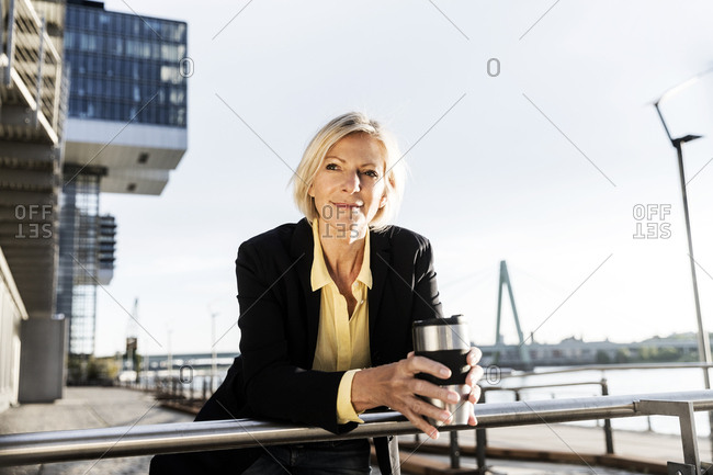 Smiling senior businesswoman with takeaway coffee at the riverside
