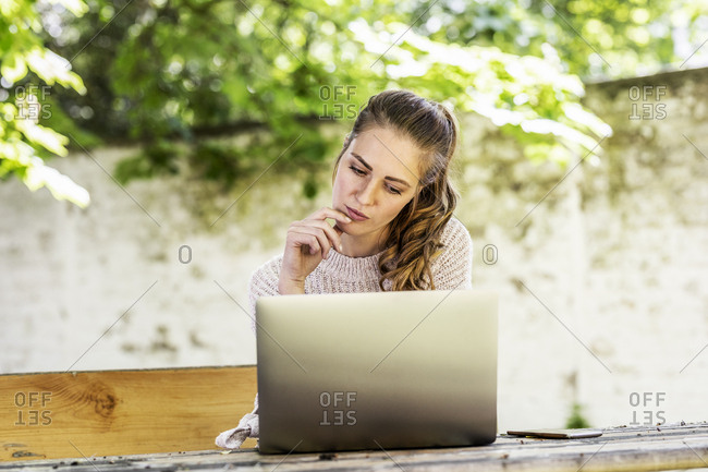 Portrait of pensive woman sitting on bench at courtyard looking at laptop