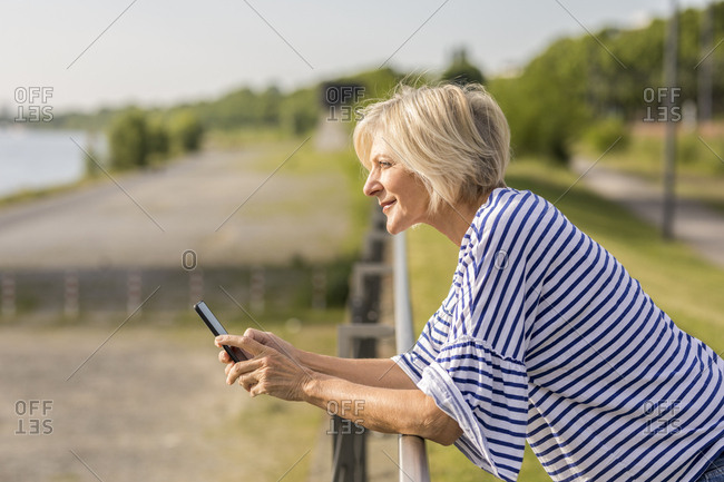 Smiling senior woman with cell phone leaning on railing at riverbank