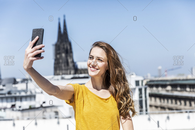 Germany- Cologne- portrait of smiling woman taking selfie with smartphone on roof terrace