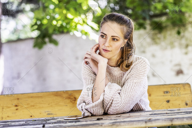 Portrait of pensive woman sitting on bench at courtyard