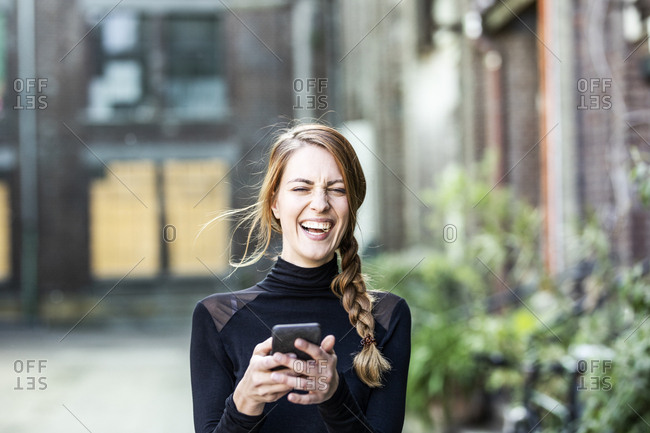 Portrait of laughing woman with smartphone