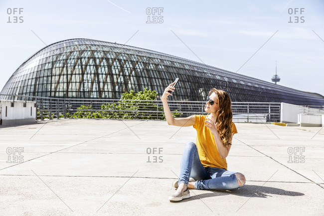 Germany- Cologne- smiling woman sitting on parking level taking selfie with smartphone