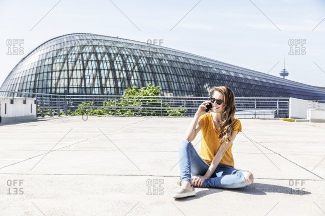 Germany- Cologne- smiling woman on the phone sitting on parking level