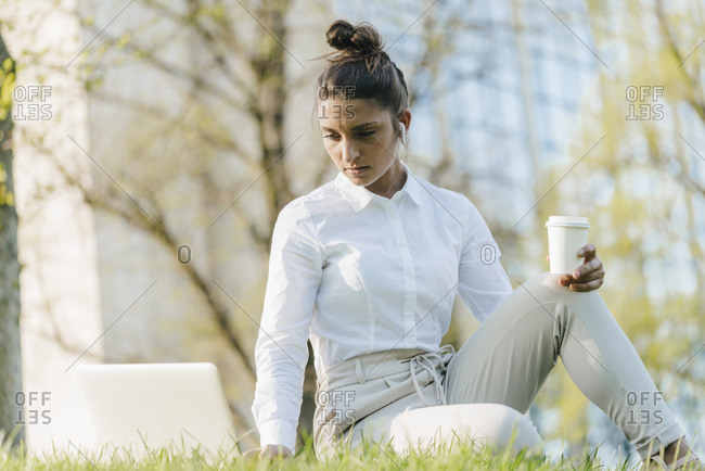 Young businesswoman taking break- using laptop- sitting in grass and drinking coffee