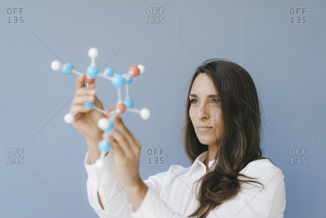 Female scientist holding molecule model- looking for solutions