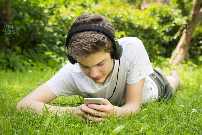 Boy lying on meadow listening music with headphones and smartphone