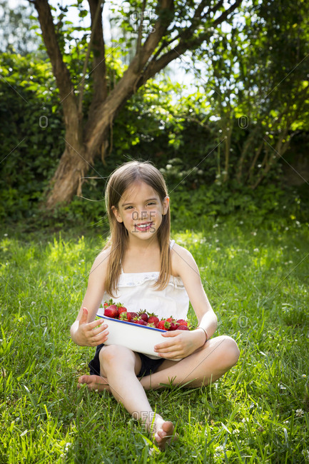 Portrait of smiling little girl sitting on meadow with bowl of strawberries