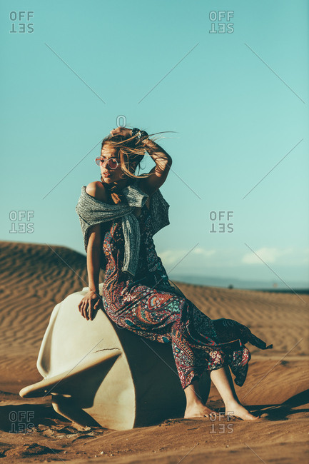 Young woman sitting in desert landscape