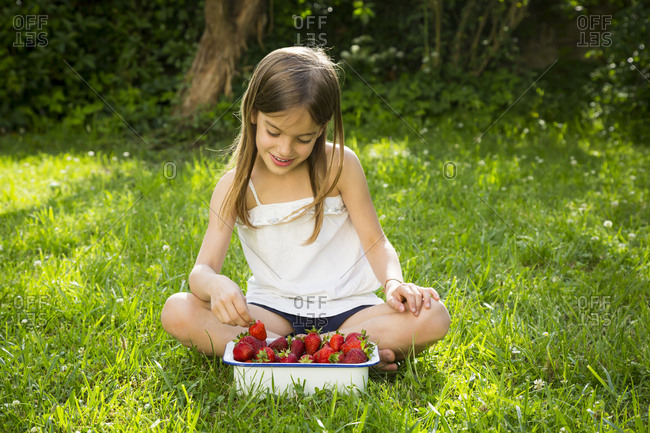 Smiling little girl sitting on meadow with bowl of strawberries