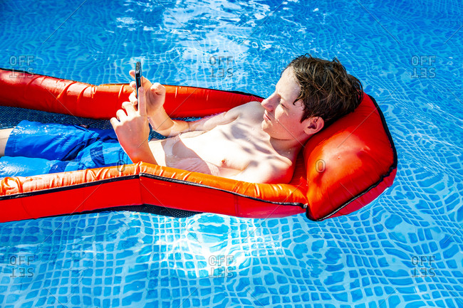 Boy floating on water in swimming pool using smartphone