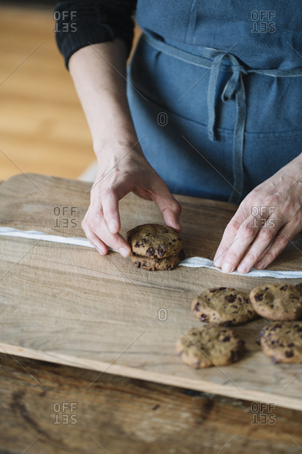 Woman's hands stacking home-baked vegan chickpea cookies- partial view