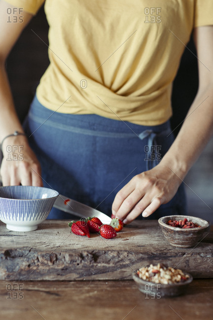 Woman preparing cutting strawberries on cutting board