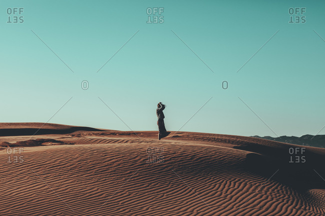 Young woman with windswept hair standing in desert landscape