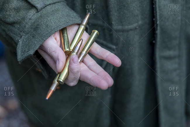 Hand of hunter holding rifle cartridges
