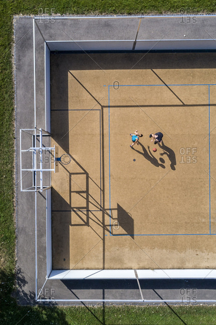 Young man and woman playing basketball- aerial view
