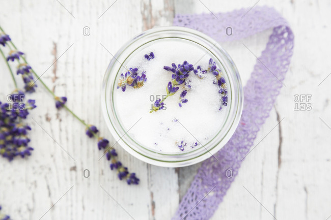 Glass of homemade lavender sugar with lavender blossoms