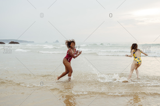 Two girls with swimsuits playing with water on the seashore