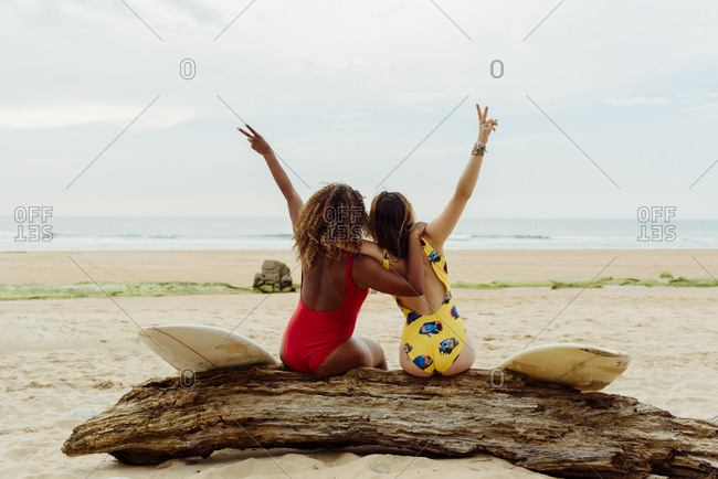 Two unrecognizable girls sitting on a trunk on the beach with surfboards greeting the sea