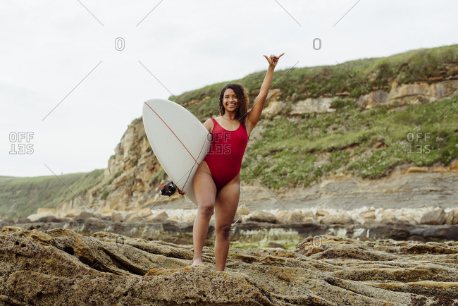 Pretty black girl with a surfboard standing on the rocks and greeting