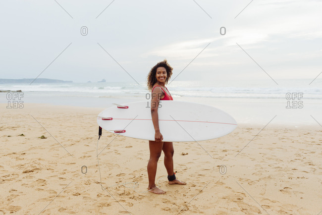 Pretty black girl standing on the beach with a surfboard looking at the camera
