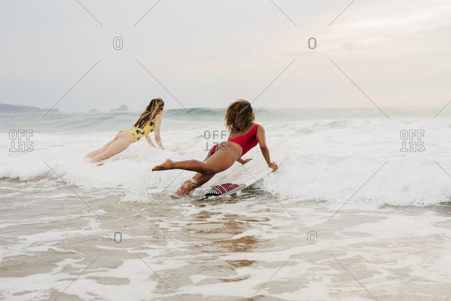 Two girls with surfboards entering the sea