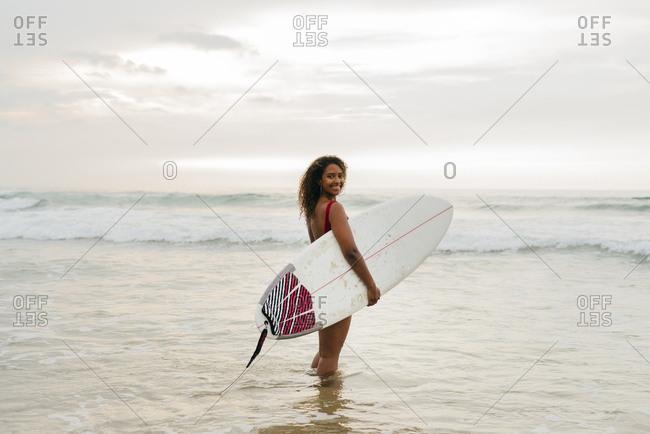 Pretty black girl standing on the seashore with a surfboard looking at the camera
