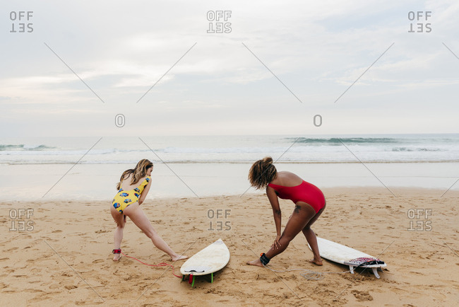 Two girls with surfboards making exercises before surfing