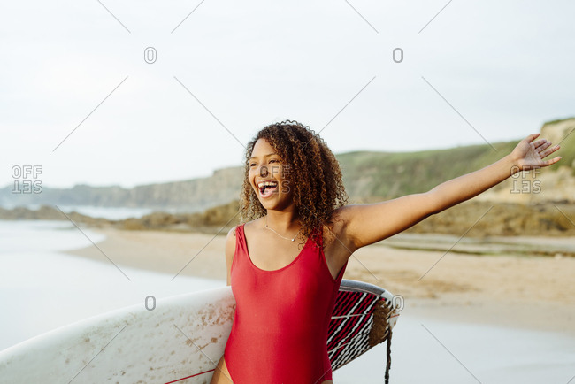 Pretty black girl standing on the seashore with a surfboard at sunset