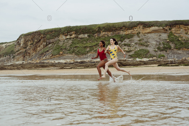 Two girls with swimsuits running on the seashore
