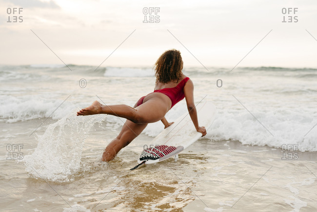 Black girl entering the sea with surfboard